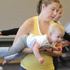 Jackie Bradley carries her daughter Avery Ditsworth, 15 months-old, as they move around the room during the Preschool Yoga/Movement session taught by Sara Guenther at the Mamie Doud Eisenhower Public Library on Saturday.<br /> <br /> November 18, 2011<br /> staff photo/ David R. Jennings