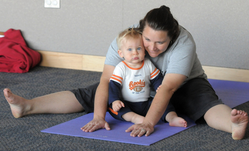 Kelleigh Betts performs yoga exercises with her son Conor, 16 months-old, during the Preschool Yoga/Movement session taught by Sara Guenther at the Mamie Doud Eisenhower Public Library on Saturday.<br /> <br /> November 18, 2011<br /> staff photo/ David R. Jennings