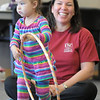 Melanie Adkins watches her daughter Madeline, 2 1/2, play with a hula hoop during the Preschool Yoga/Movement session taught by Sara Guenther at the Mamie Doud Eisenhower Public Library on Saturday.<br /> <br /> November 18, 2011<br /> staff photo/ David R. Jennings