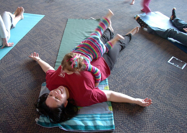 Melanie Adkins and her daughter Madeline, 2 1/2, perform a calming yoga exercise during the Preschool Yoga/Movement session taught by Sara Guenther at the Mamie Doud Eisenhower Public Library on Saturday.<br /> <br /> November 18, 2011<br /> staff photo/ David R. Jennings