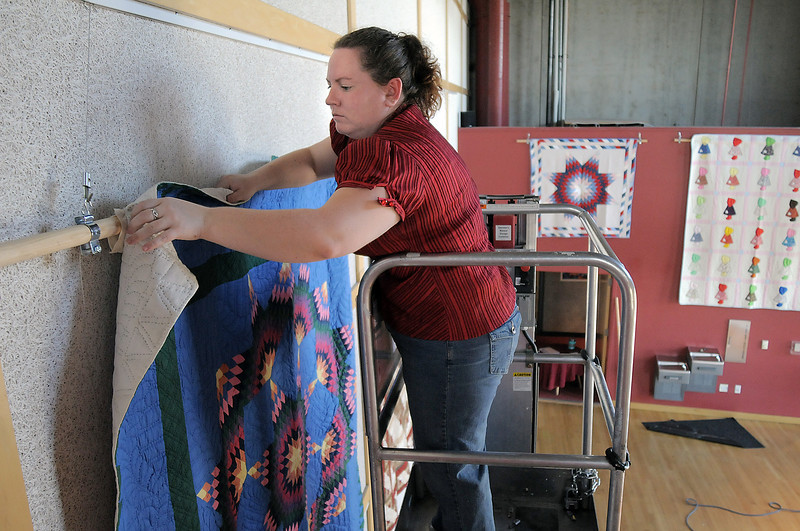 Amy Edel works on hanging a quilt in the lobby of the Audi for the quilt exibit for the Aster Women's Choir productin of Quilters.<br /> <br /> September 2, 2011<br /> staff photo/ David R. Jennings