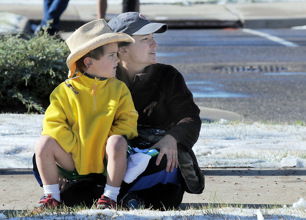 Sammy Carpenter, 5, and his mother Michelle watch racers in the 5K run during the Frank Shorter Race 4 Kid's Health a Broomfield Rotary fundraiser for Healthy Learning Paths at the Broomfield County Commons on Sunday.<br /> April 10, 2011<br /> staff photo/David R. Jennings