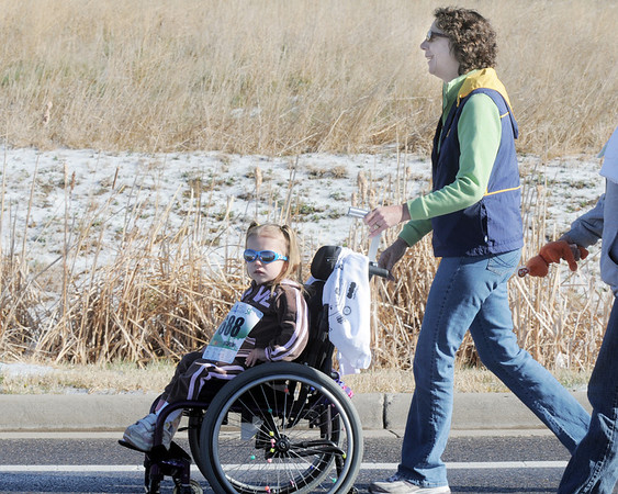 Sara Frey, 4, walks with her grandmother Maureen Voss in the 5K run during the Frank Shorter Race 4 Kid's Health a Broomfield Rotary fundraiser for Healthy Learning Paths at the Broomfield County Commons on Sunday.<br /> April 10, 2011<br /> staff photo/David R. Jennings
