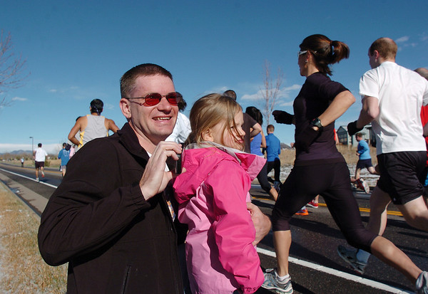 Kurt Schmidt and his daughter Abigail, 3, watch for wife/mom Jennifer  running in the 5K during the Frank Shorter Race 4 Kid's Health a Broomfield Rotary fundraiser for Healthy Learning Paths at the Broomfield County Commons on Sunday.<br /> April 10, 2011<br /> staff photo/David R. Jennings