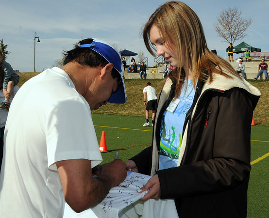 Brittany Mohler holds a t-shirt for Carlos Perez to sign which will be given to Olympic gold Medalist Frank Shorter at the Race4Kids' Health 5K run at Broomfield County Commons Park on Sunday.<br /> <br /> April 11, 2010<br /> Staff photo/David R. Jennings