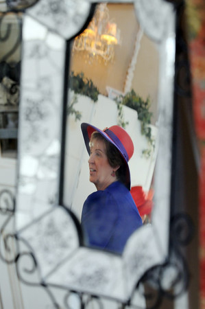 Donna Eads is reflected in a mirror while having lunch at the meeting of the Red Hat Society's chapter the Red Hat Showoffs at the Rustic Ranch.<br /> <br /> November 12, 2009<br /> Staff photo/David R. Jennings