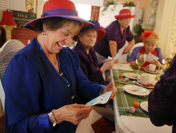 Donna Eads laughs at a funny gift at the meeting of the Red Hat Society's chapter the Red Hat Showoffs at the Rustic Ranch.<br /> <br /> November 12, 2009<br /> Staff photo/David R. Jennings