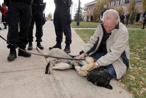 Doug Collins, the father of retiring Broomfield Police officer Jason Collins, plays with Nik, Jason's K-9 dog who is also retiring, after the retirement ceremony in front of police headquarters on Wednesday.<br /> Doug Colllins said he and Nik have become good buddies.<br /> <br /> December 1, 2010<br /> staff photo/David R. Jennings