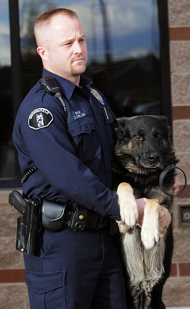 Retiring Broomfeild Police officer Jason Collins holds his K-9 dog Nik  during the retirement ceremony for both Collins and Nik in front of  police headquarters on Wednesday.<br /> <br /> December 1, 2010<br /> staff photo/David R. Jennings