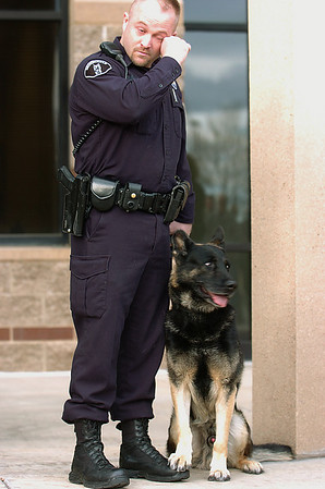 Broomfield Police officer Jason Collins tries to hold back tears while standing with his K-9 dog Nik during the retirement ceremony for Collins and Nik in front of the police headquarters on Wednesday.<br /> <br /> December 1, 2010<br /> staff photo/David R. Jennings