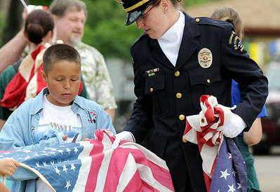 Emil Gimeno, 10, gets some help from Broomfield Police officer Carol Lucero during Thursday's 5th annual Broomfield Veteran's Museum and North Metro Fire Rescue flag retirement ceremony at North Metro Fire Rescue Station 61 in Broomfield.  July 2, 2009 staff photo/David R. Jennings