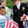 Emil Gimeno, 10, gets some help from Broomfield Police officer Carol Lucero during Thursday's 5th annual Broomfield Veteran's Museum and North Metro Fire Rescue flag retirement ceremony at North Metro Fire Rescue Station 61 in Broomfield.<br /> <br /> July 2, 2009<br /> staff photo/David R. Jennings