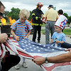 Firefighter Doug Finley, left, and Paramedic Mark Sherman hold a flag for Martin Forbes, 7, and his brother Joe Forbes, 2,  to cut in preparation for burning at the 5th annual Broomfield Veteran's Museum and North Metro Fire Rescue flag retirement ceremony at North Metro Fire Rescue Station 61 in Broomfield.<br /> <br /> July 2, 2009<br /> staff photo/David R. Jennings