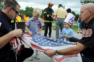 Firefighter Doug Finley, left, and Paramedic Mark Sherman hold a flag for Martin Forbes, 7, and his brother Joe Forbes, 2,  to cut in preparation for burning at the 5th annual Broomfield Veteran's Museum and North Metro Fire Rescue flag retirement ceremony at North Metro Fire Rescue Station 61 in Broomfield.  July 2, 2009 staff photo/David R. Jennings