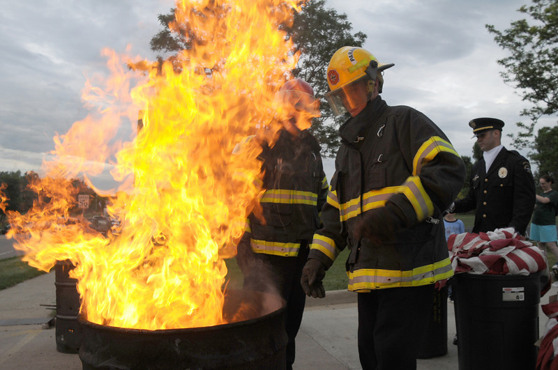 Firefighters keep watch over the barrels where the flags are burned during the retirement ceremony at North Metro Fire Rescue Station 61 in Broomfield.<br /> <br /> July 2, 2009<br /> staff photo/David R. Jennings