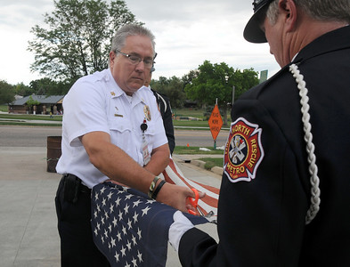 North Metro Fire Rescue Chief Joe Bruce, left, cuts a flag held by Lt. Curtis Kantz during the flag retirement ceremony at North Metro Fire Rescue Station 61 in Broomfield.  July 2, 2009 staff photo/David R. Jennings