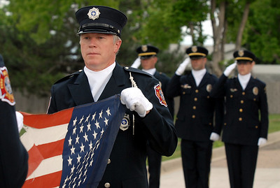 North Metro Lt. Curtis Kantz holds a flag to be retired while the Broomfield Police honor guard salutes during Thursday's 5th annual Broomfield Veteran's Museum and North Metro Fire Rescue flag retirement ceremony at North Metro Fire Rescue Station 61 in Broomfield.  July 2, 2009 staff photo/David R. Jennings