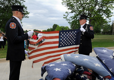 Paramedic Ken Work, left, and Lt. Curtis Kantz display a flag that represents the 551 flags being retired at Thursday's 5th annual Broomfield Veteran's Museum and North Metro Fire Rescue flag retirement ceremony at North Metro Fire Rescue Station 61 in Broomfield.  July 2, 2009 staff photo/David R. Jennings