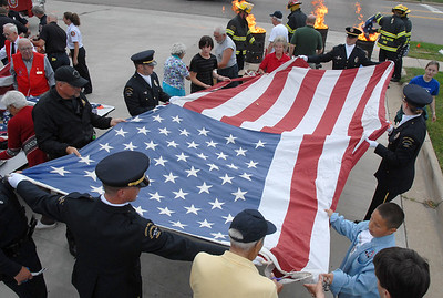A large flag is unfurled in preparation for the field of stars to be removed during Thursday's 5th annual Broomfield Veteran's Museum and North Metro Fire Rescue flag retirement ceremony at North Metro Fire Rescue Station 61 in Broomfield.  July 2, 2009 staff photo/David R. Jennings