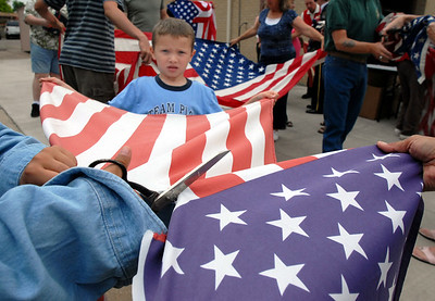 Jacob Krol, 6, helps hold a flag while Emil Gimeno, 10, cuts the frild of stars from the flag for retirement during the ceremony at North Metro Fire Rescue Station 61 in Broomfield.  July 2, 2009 staff photo/David R. Jennings