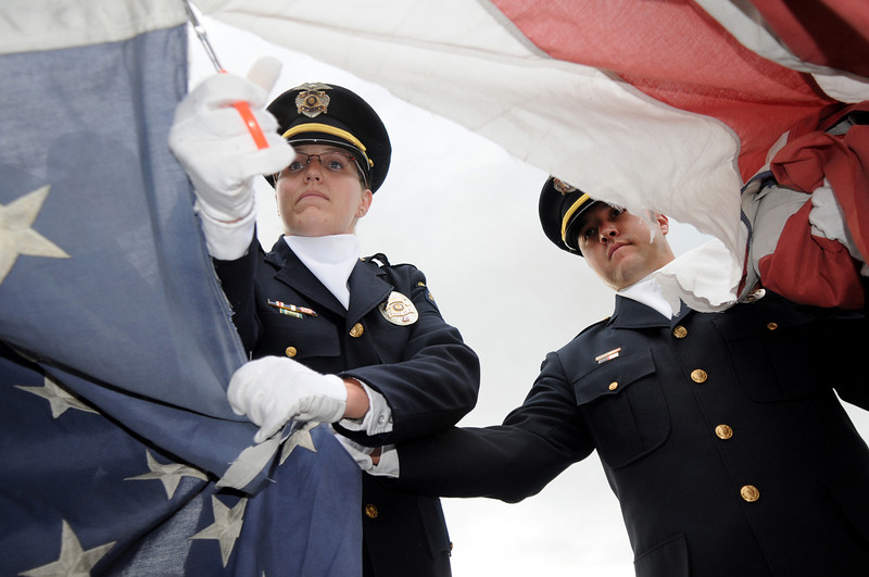 Broomfield Police officers Carol Lucero, left, and John Frahm cut the field of stars from a flag during Thursday's 5th annual Broomfield Veteran's Museum and North Metro Fire Rescue flag retirement ceremony at North Metro Fire Rescue Station 61 in Broomfield.<br /> <br /> July 2, 2009<br /> staff photo/David R. Jennings