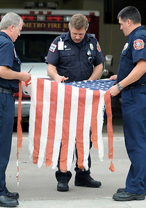 North Metro Fire Rescue firefighter Steve Markham, center, cuts a flag with the help of Lt. Curtis Kantz, left, and firefighter Steve Bostwick during Thursday's 5th annual Broomfield Veteran's Museum and North Metro Fire Rescue flag retirement ceremony at North Metro Fire Rescue Station 61 in Broomfield.  July 2, 2009 staff photo/David R. Jennings