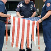North Metro Fire Rescue firefighter Steve Markham, center, cuts a flag with the help of Lt. Curtis Kantz, left, and firefighter Steve Bostwick during Thursday's 5th annual Broomfield Veteran's Museum and North Metro Fire Rescue flag retirement ceremony at North Metro Fire Rescue Station 61 in Broomfield.<br /> <br /> July 2, 2009<br /> staff photo/David R. Jennings