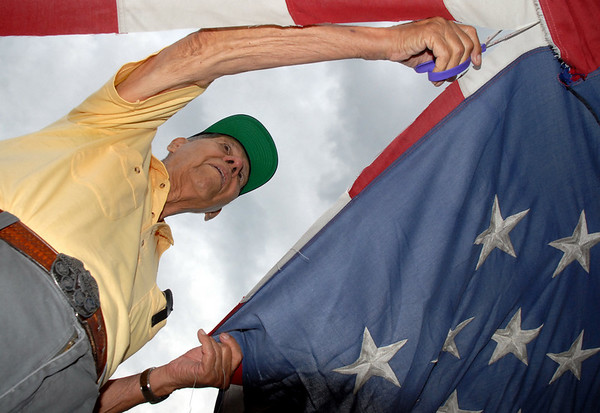 World War II veteran Emil Gimeno, 88, cuts the field of stars from a flag during Thursday's 5th annual Broomfield Veteran's Museum and North Metro Fire Rescue flag retirement ceremony at North Metro Fire Rescue Station 61 in Broomfield.<br /> <br /> July 2, 2009<br /> staff photo/David R. Jennings