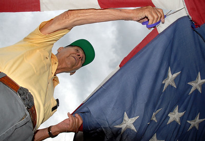 World War II veteran Emil Gimeno, 88, cuts the field of stars from a flag during Thursday's 5th annual Broomfield Veteran's Museum and North Metro Fire Rescue flag retirement ceremony at North Metro Fire Rescue Station 61 in Broomfield.  July 2, 2009 staff photo/David R. Jennings