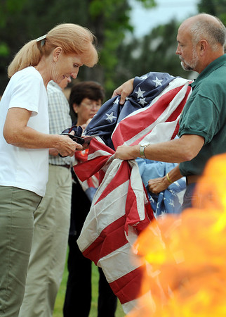 Sandy and Bob Akmenkalns work on cutting the field of stars from a flag during Thursday's 5th annual Broomfield Veteran's Museum and North Metro Fire Rescue flag retirement ceremony at North Metro Fire Rescue Station 61 in Broomfield.<br /> <br /> July 2, 2009<br /> staff photo/David R. Jennings