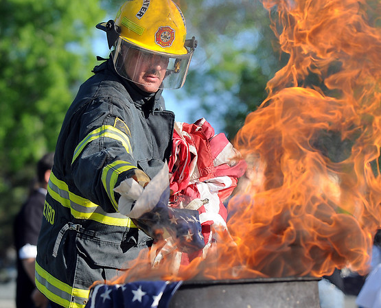 Firefighter Stephen Bostwick places the stars into a fire while holding the strips to be burned separately during the 2010 Flag Retirement Ceremony at North Metro Fire Station 61 on Monday, Flag Day.  North Metro Fire Rescue and the Broomfield Veteran's Memorial Museum sponsored the Flag Day event.<br /> <br /> June 14, 2010<br /> Staff photo/ David R. Jennings