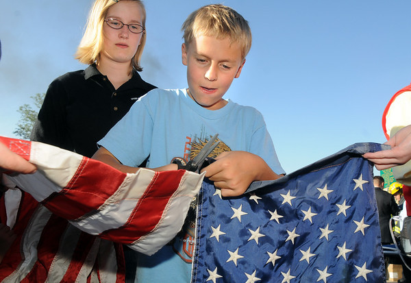 Calvin Reynolds, 11, cuts the stars from the strips of a flag as Amanda Reynolds, 13, helps during the 2010 Flag Retirement Ceremony at North Metro Fire Station 61 on Monday, Flag Day.  North Metro Fire Rescue and the Broomfield Veteran's Memorial Museum sponsored the Flag Day event.<br /> <br /> June 14, 2010<br /> Staff photo/ David R. Jennings