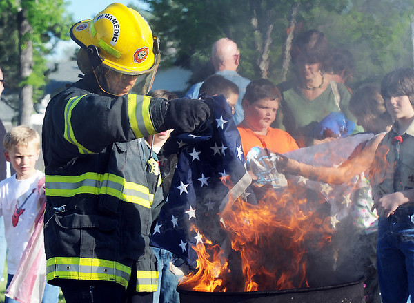 North Metro Fire Rescue Paramedic Jeff Tipton places the stars form flages into the fire during the 2010 Flag Retirement Ceremony at North Metro Fire Station 61 on Monday, Flag Day.  North Metro Fire Rescue and the Broomfield Veteran's Memorial Museum sponsored the Flag Day event.<br /> <br /> June 14, 2010<br /> Staff photo/ David R. Jennings