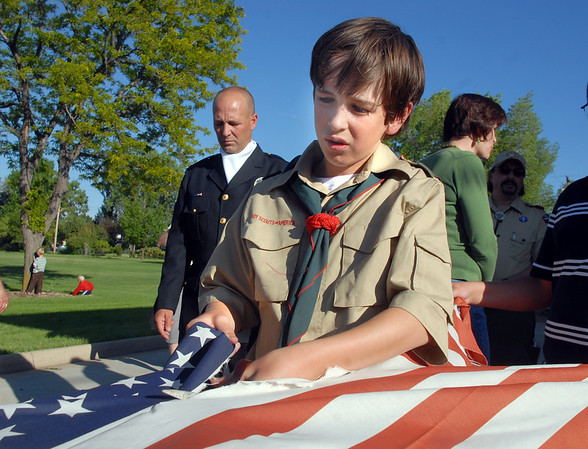 Boy Scout Bryan Zayach, 12, with Troop 511, cuts a flag to separate the stars for the strips during the 2010 Flag Retirement Ceremony at North Metro Fire Station 61 on Monday, Flag Day.  North Metro Fire Rescue and the Broomfield Veteran's Memorial Museum sponsored the Flag Day event.<br /> <br /> June 14, 2010<br /> Staff photo/ David R. Jennings
