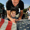 Cory Vanzant and his son Landon, 3, cut a flag to separate the stars from the strips during the 2010 Flag Retirement Ceremony at North Metro Fire Station 61 on Monday, Flag Day.  North Metro Fire Rescue and the Broomfield Veteran's Memorial Museum sponsored the Flag Day event.<br /> <br /> June 14, 2010<br /> Staff photo/ David R. Jennings