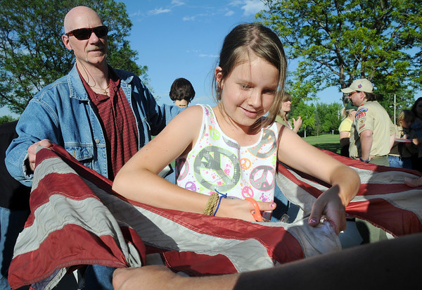 Ruth McCulloch, 10, cuts away the strips from a flag as her father Bill holds the flag during the 2010 Flag Retirement Ceremony at North Metro Fire Station 61 on Monday, Flag Day.  North Metro Fire Rescue and the Broomfield Veteran's Memorial Museum sponsored the Flag Day event.<br /> <br /> June 14, 2010<br /> Staff photo/ David R. Jennings