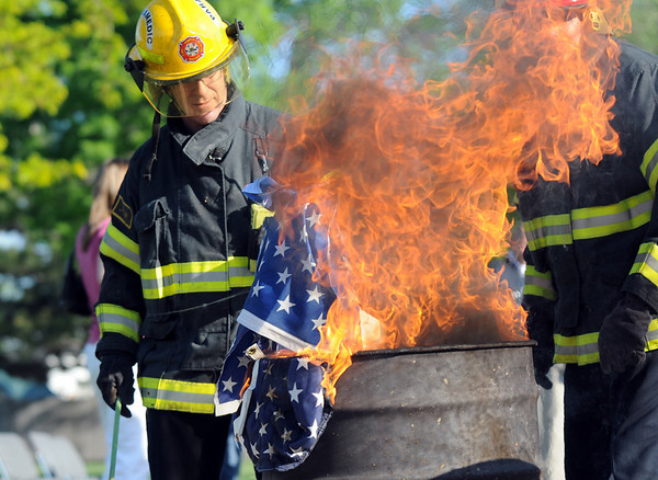 North Metro Fire Rescue Paramedic Jeff Tipton places the stars of flags into the fire during the 2010 Flag Retirement Ceremony at North Metro Fire Station 61 on Monday, Flag Day.  North Metro Fire Rescue and the Broomfield Veteran's Memorial Museum sponsored the Flag Day event.<br /> <br /> June 14, 2010<br /> Staff photo/ David R. Jennings