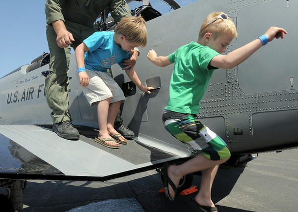 Noah Parker, 7, right, and his brother Dawson, 5, jump off of the wing of a U.S. Airforce trainer airplane during Saturday's Rocky Mountain Airshow at Rocky Mountain Metropolitan Airport.<br /> August 27, 2011<br /> staff photo/ David R. Jennings