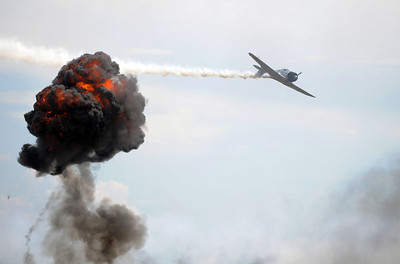 A Japanese World War II plane flies past an explosion for a reenactment of the Pearl Harbor attack during Saturday's Rocky Mountain Airshow at Rocky Mountain Metropolitan Airport. August 27, 2011 staff photo/ David R. Jennings