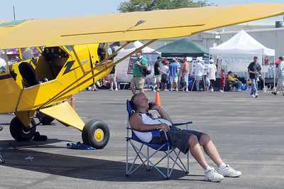 John Barrett stays in the shade of his Piper airplane during Saturday's Rocky Mountain Airshow at Rocky Mountain Metropolitan Airport. August 27, 2011 staff photo/ David R. Jennings