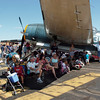 Airshow fans watch the aircraft perfomances in the shade of an airplane during Saturday's Rocky Mountain Airshow at Rocky Mountain Metropolitan Airport.<br /> August 27, 2011<br /> staff photo/ David R. Jennings