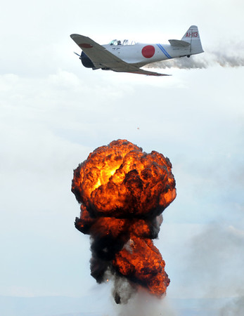 A World War II Japanese Zero flies near a firey blast simulating explosions during Tora Tora Tora re-enacment of the bombing of Pearl Harbor at Saturday's Rocky Mountain Airshow at Rocky Mountain Metropolitan Airport.<br /> August 27, 2011<br /> staff photo/ David R. Jennings