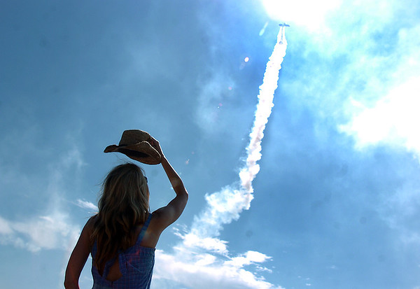 Dena Douglas from Arvada watches a Stearman airplane perform during Saturday's Rocky Mountain Airshow at Rocky Mountain Metropolitan Airport.<br /> August 27, 2011<br /> staff photo/ David R. Jennings