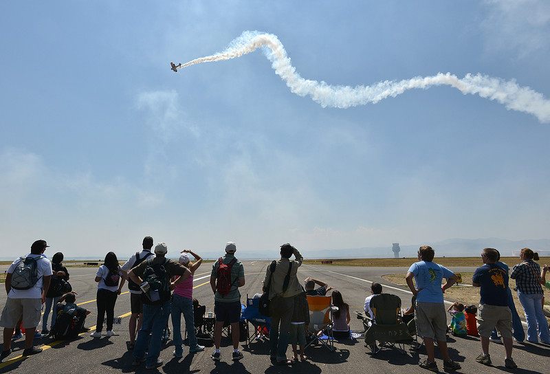 Airshow fans watch a plane perform during Saturday's Rocky Mountain Airshow 2012 at Rocky Mountain Metropolitan Airport. <br /> <br /> August 26, 2012<br /> staff photo/ David R. Jennings