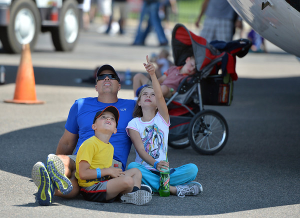 Ike Nissen with his children Tanner, 6, left, and Logan, 9, from Berthoud, watch planes perform while sitting in the shadow of NCAR's Snowflake C-130 during Saturday's Rocky Mountain Airshow 2012 at Rocky Mountain Metropolitan Airport. <br /> <br /> August 26, 2012<br /> staff photo/ David R. Jennings