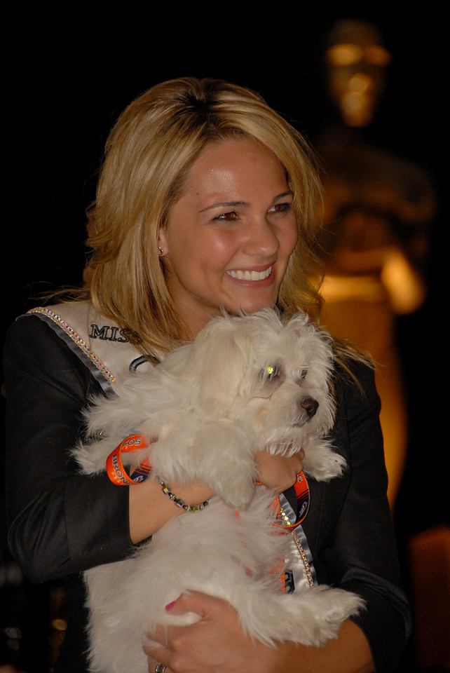 Miss Teen Colorado Courtney Carter cuddles with Tebow, one of two puppies that were auctioned off to support A Precious Child during Odyssey 2010 on Friday.
