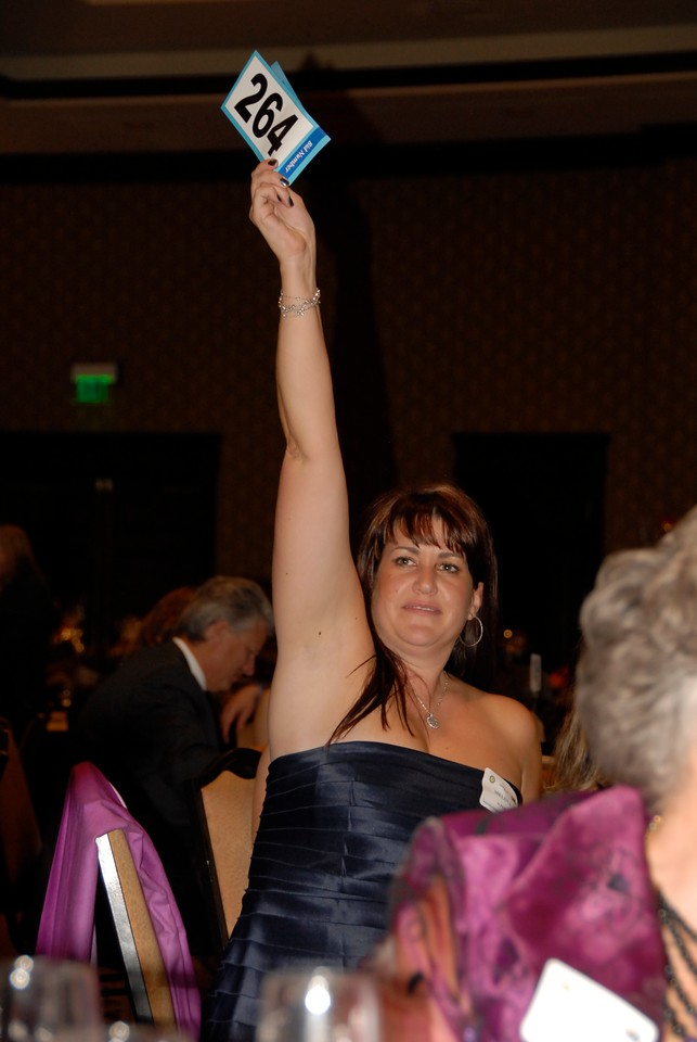 Melissa Alpert, owner of Huntington Learning Center, bids on an auction item during Odyssey 2010.
