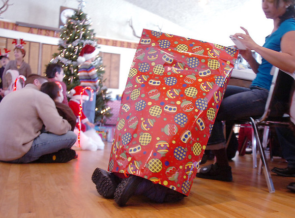 Bal Swan Children's Center student Harman Saron, 4, plays in the gifts bag after receiving a gift from Santa at the Louisville Elk's Lodge for the Santa Run on Saturday.<br /> For more photos please see broomfieldenterprise.com.<br /> December 3, 2011<br /> staff photo/ David R. Jennings