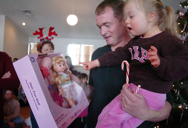 Bal Swan Children's Center student Lydia Triplett, 3, and her father Matt look at her present she received from Santa at the Louisville Elk's Lodge for the Santa Run on Saturday.<br /> For more photos please see broomfieldenterprise.com.<br /> December 3, 2011<br /> staff photo/ David R. Jennings