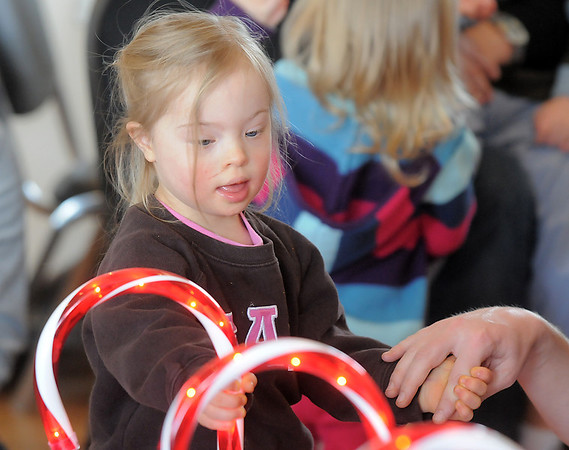 Bal Swan Children's Center student Lydia Triplett, 3, looks at the lighted candy canes before receiving a gift from Santa at the Louisville Elk's Lodge for the Santa Run on Saturday.<br /> For more photos please see broomfieldenterprise.com.<br /> December 3, 2011<br /> staff photo/ David R. Jennings